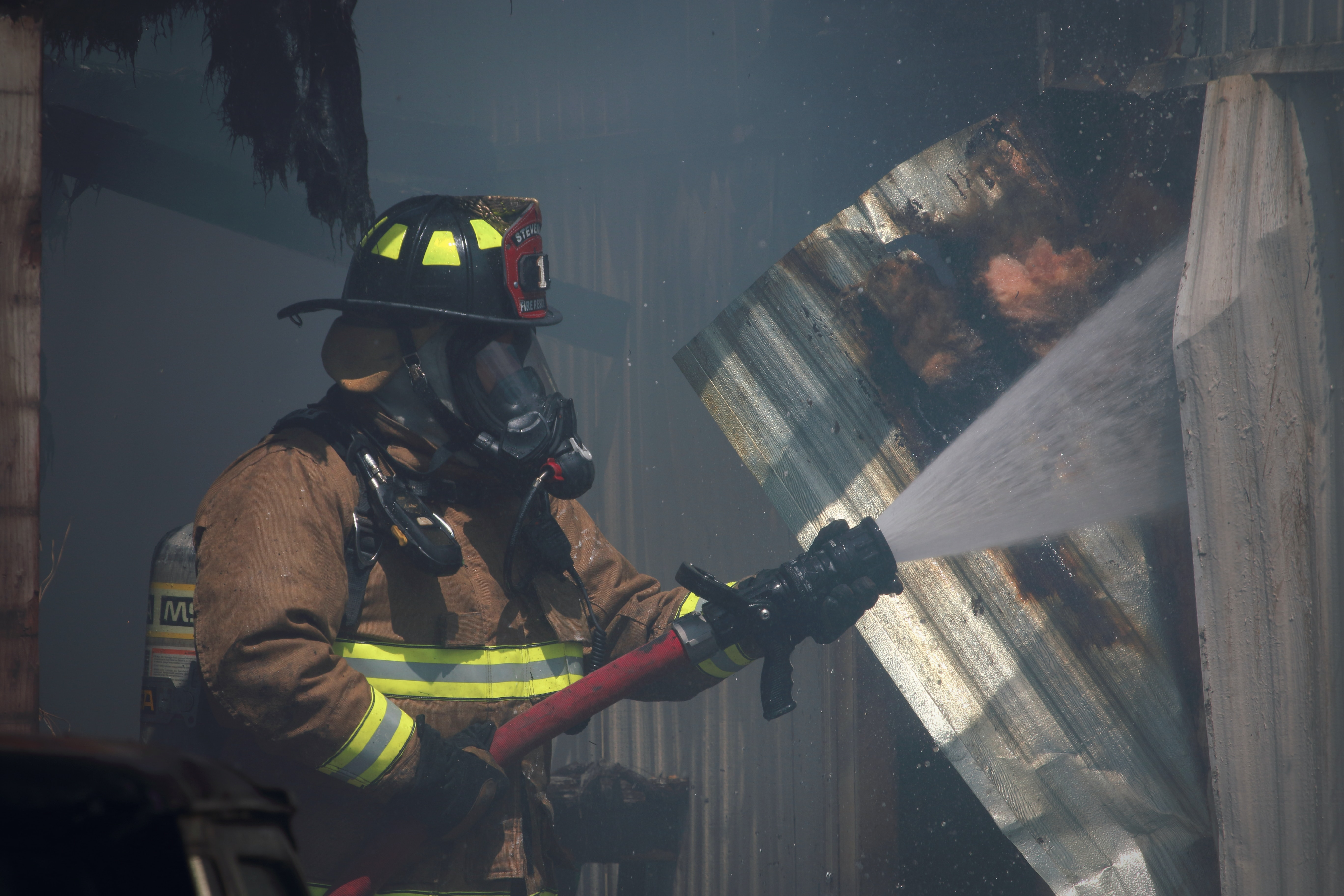 shallow focus photo of firefighter using red water hose